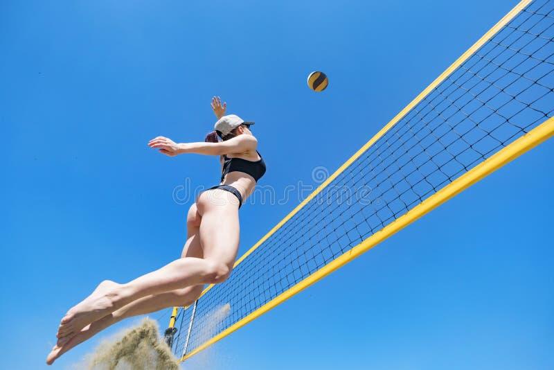 Salto de la chica joven, jugando a voleibol en la playa Concepto de forma de vida sana Bloqueo de la bola imagen de archivo libre de regalías