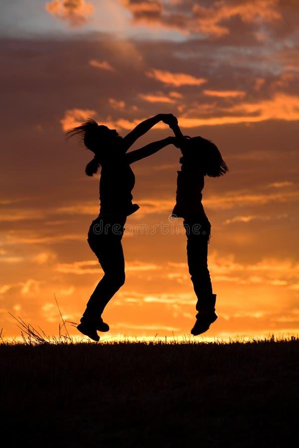 Salto de la madre y de la hija en la puesta del sol. fotografía de archivo