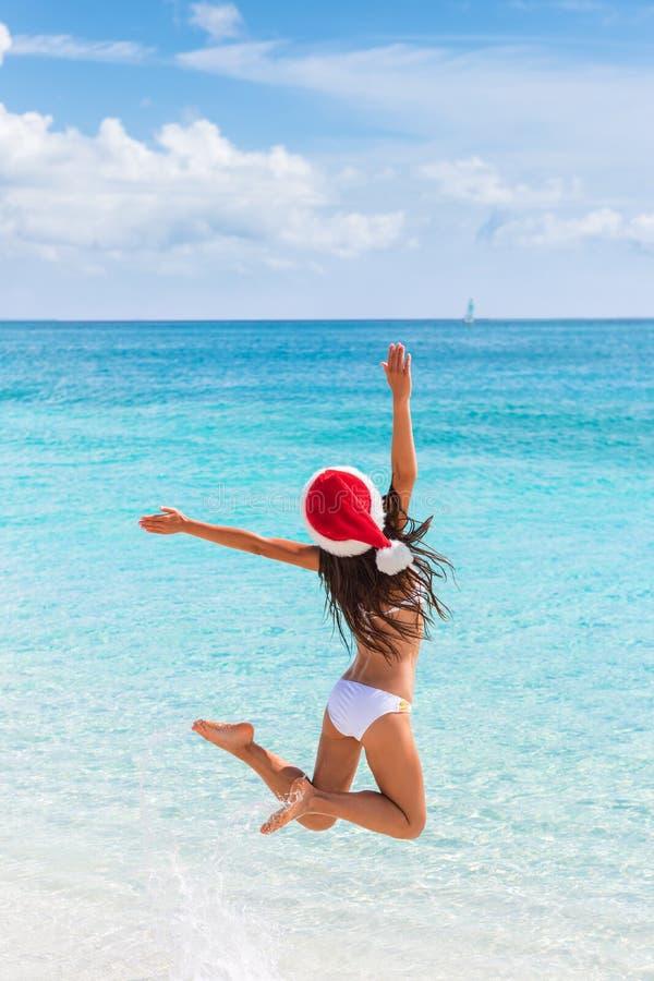 Salto de la muchacha del sombrero de la feliz Navidad de la alegría en la playa imagen de archivo