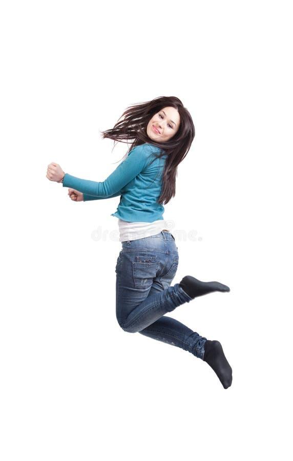 Salto de la mujer joven alegre feliz imagen de archivo