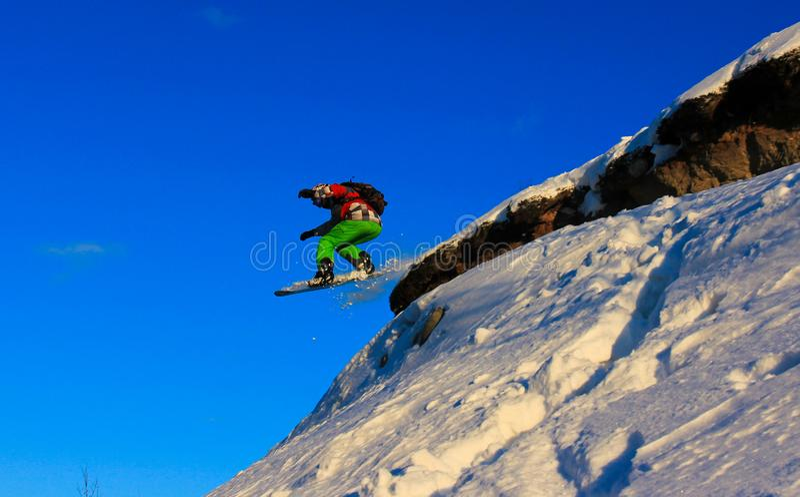 Salto de la snowboard de un acantilado imagen de archivo libre de regalías