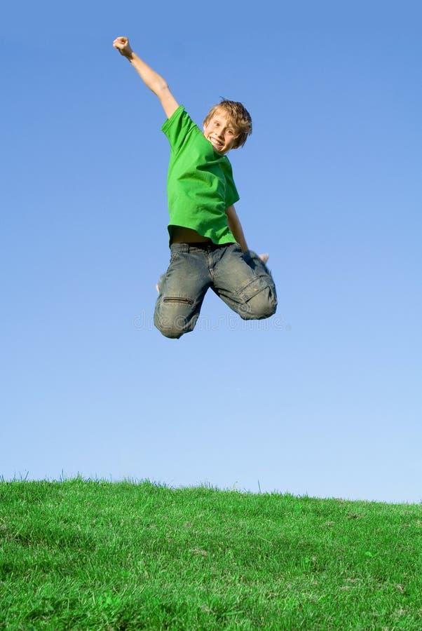 Salto de sorriso feliz da criança fotografia de stock