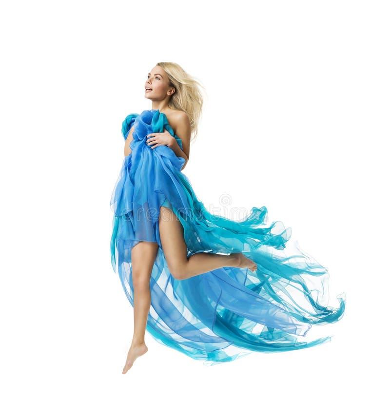 Salto de vuelo de la mujer, modelo de moda activo Jumping en vestido azul fotos de archivo