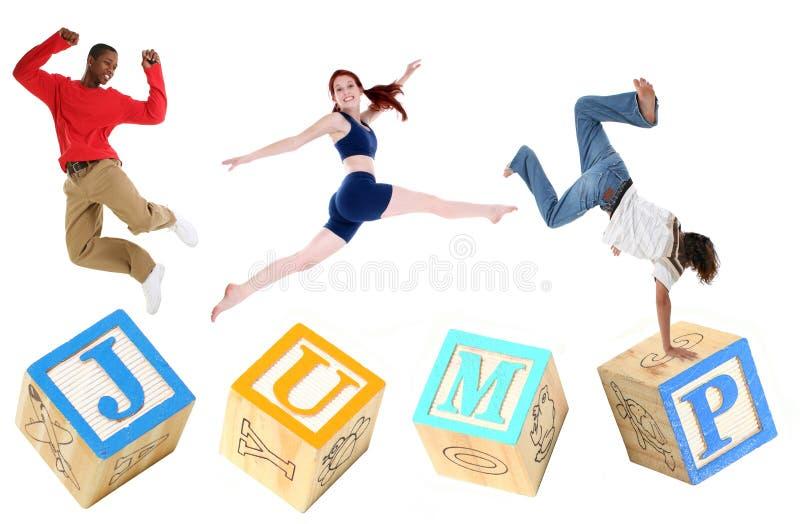 SALTO dei blocchetti di alfabeto con il salto della gente fotografia stock