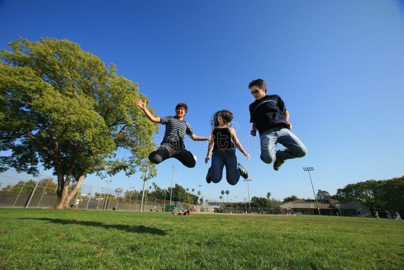 Salto dei tre un giovane amici fotografia stock libera da diritti