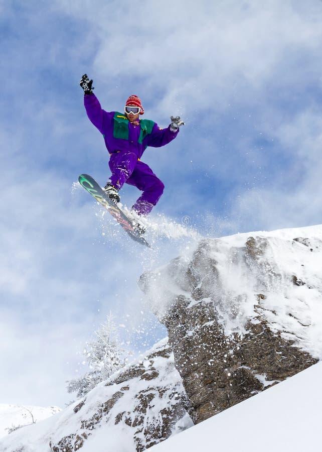 Salto del acantilado de la snowboard imagenes de archivo