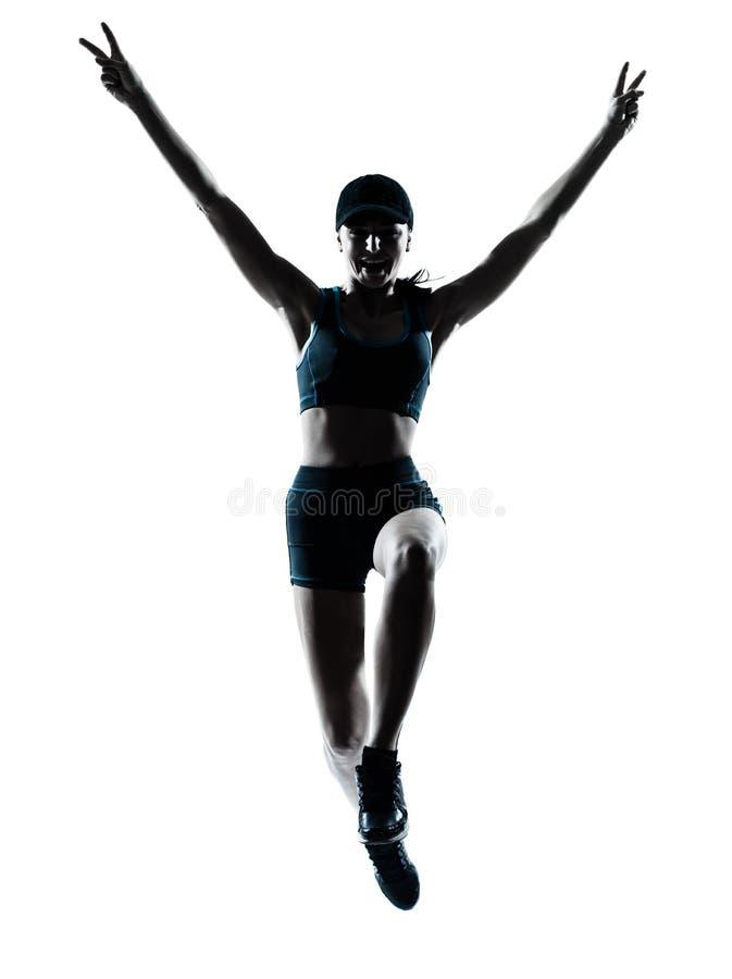 Salto del basculador del corredor de la mujer victorioso fotografía de archivo