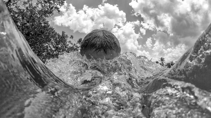 Salto del hombre en la playa Chapoteo en el agua imagenes de archivo