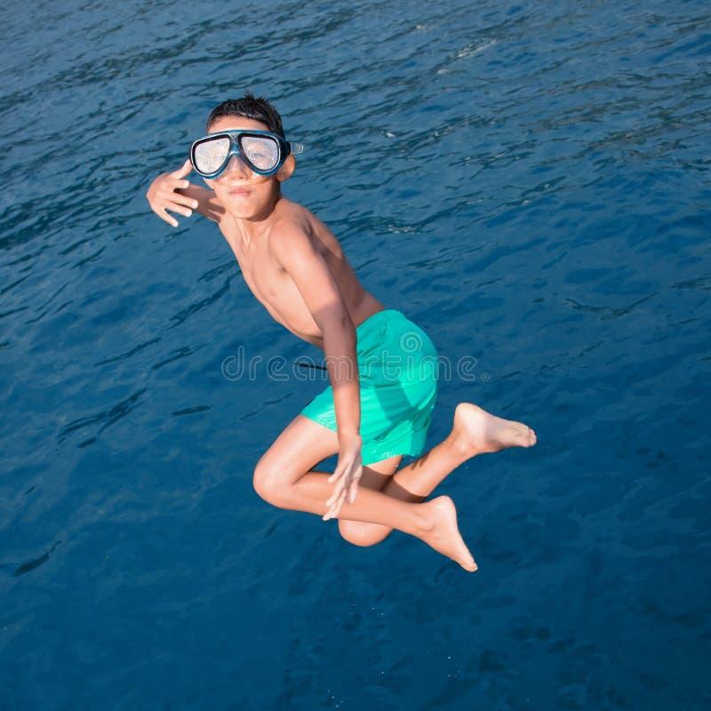 Salto del niño en el mar imagen de archivo libre de regalías