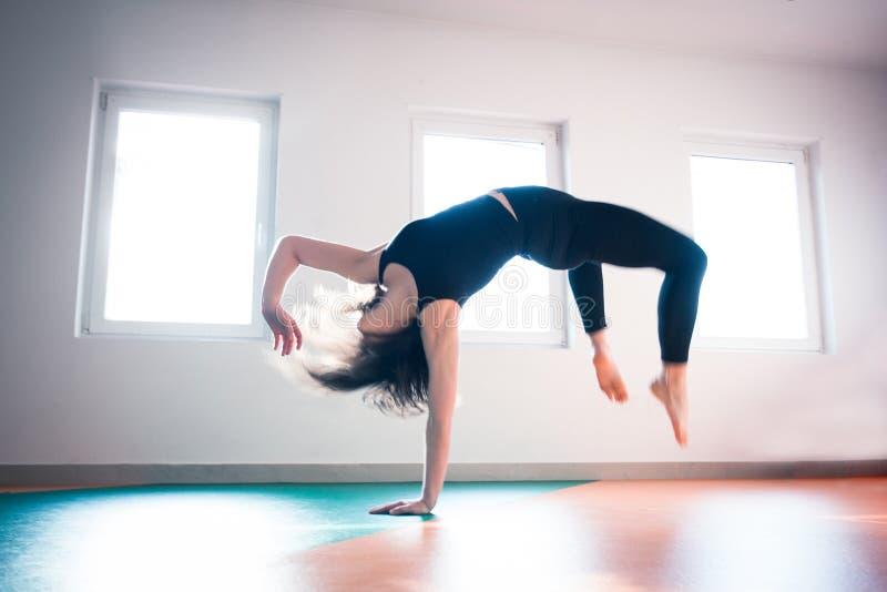 Salto del piso de la práctica del bailarín de la mujer en clase del ballet fotos de archivo