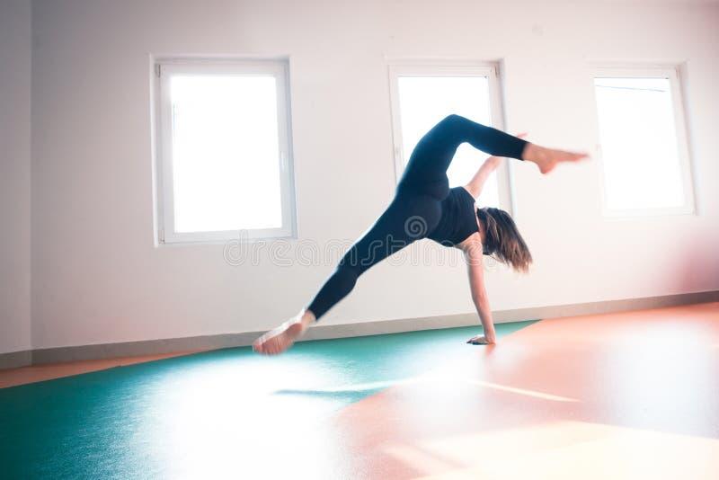 Salto del piso de la práctica del bailarín de la mujer en clase del ballet foto de archivo libre de regalías