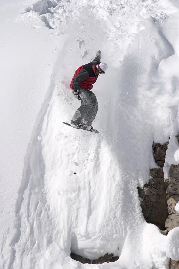 Salto del Snowboard de un acantilado en el polvo imagenes de archivo