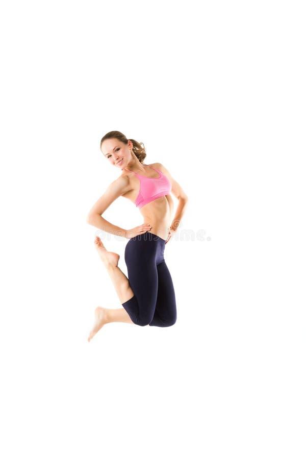 Salto della donna di forma fisica di perdita di peso della gioia Giovane modello femminile caucasico sportivo isolato su fondo bi fotografia stock