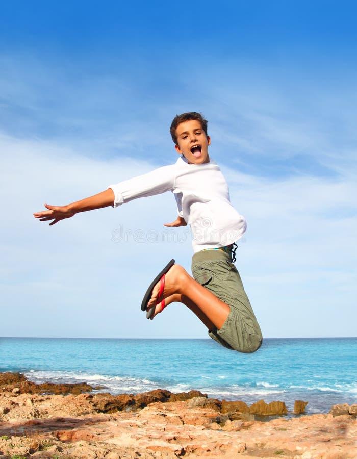 Salto della mosca dell'adolescente del ragazzo alto sul cielo blu della spiaggia fotografia stock