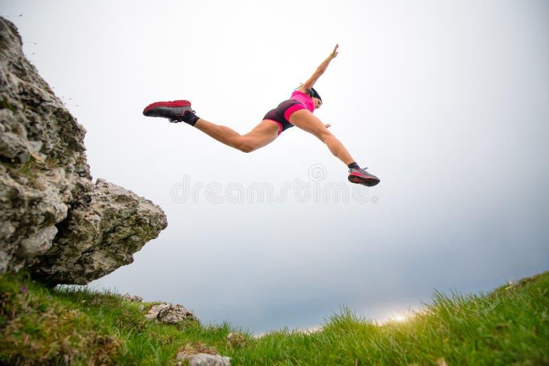Salto di un atleta sportivo della donna che corre nelle montagne fotografia stock