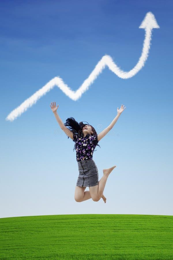 Salto do sucesso da mulher de negócios na nuvem do gráfico de lucro imagem de stock royalty free