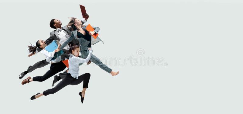 Salto dos trabalhadores de escritório isolado no fundo do estúdio imagem de stock royalty free