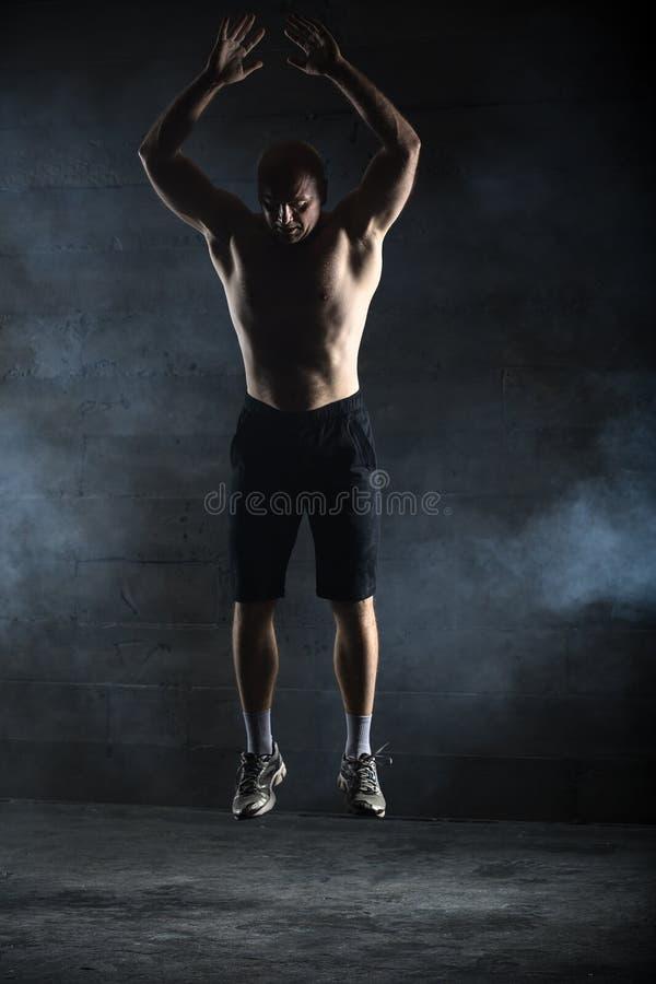 Salto em topless do atleta calvo acima imagem de stock royalty free