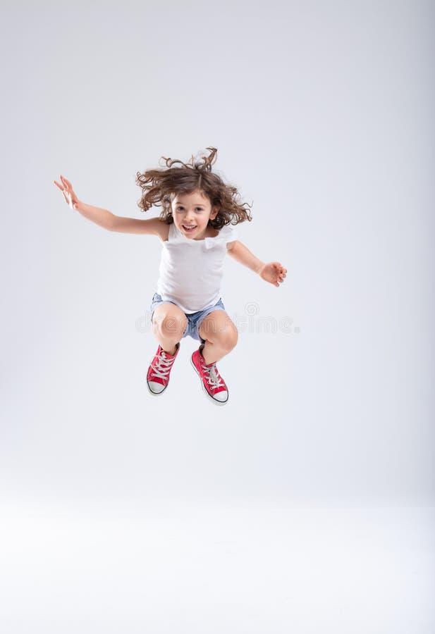 Salto enérgico de la niña alto en el aire fotografía de archivo