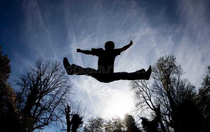 Salto en el trampolín en cielo azul imagen de archivo