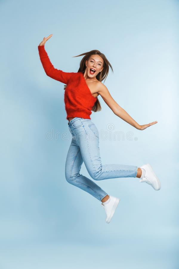 Salto entusiasmado bonito da jovem mulher isolado sobre o fundo azul da parede fotos de stock royalty free