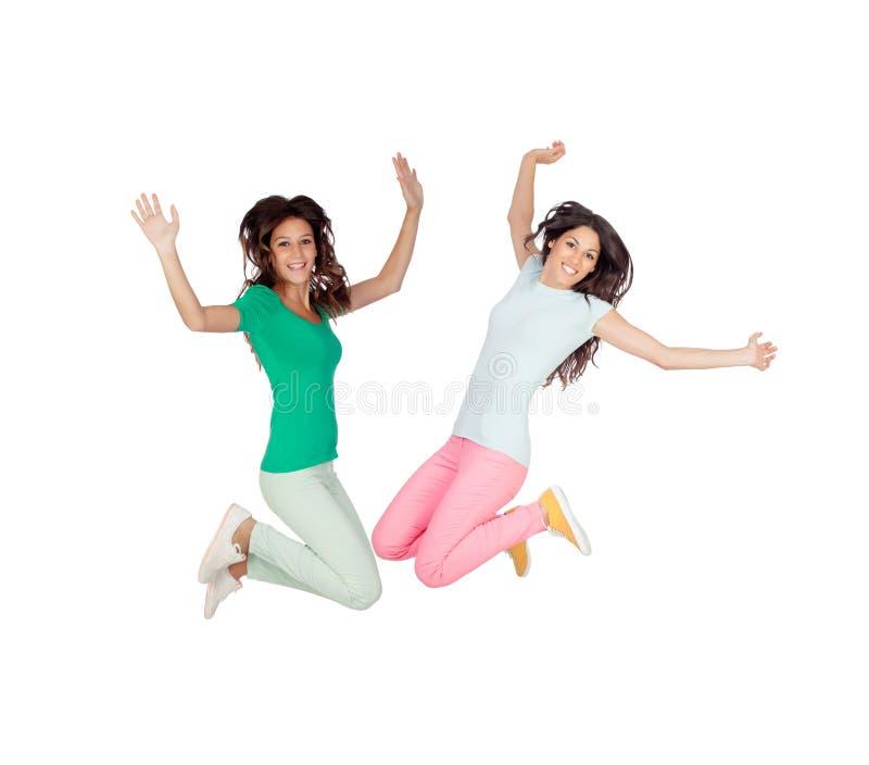 Salto entusiasmado feliz de duas jovens mulheres fotografia de stock royalty free