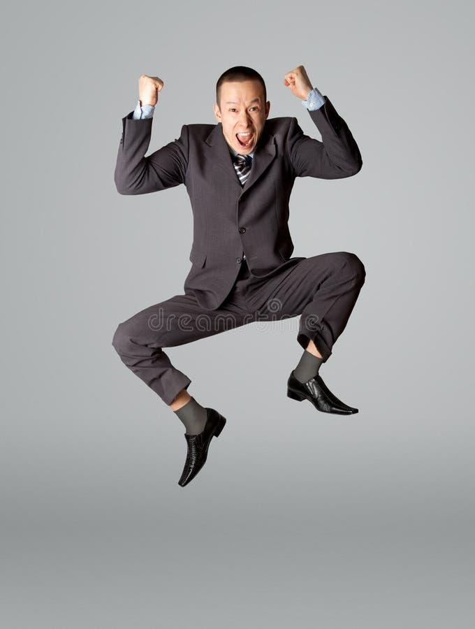 Salto felice dell'uomo d'affari fotografia stock