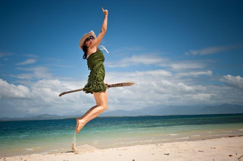 Salto felice della ragazza creativa alla spiaggia tropicale immagini stock libere da diritti
