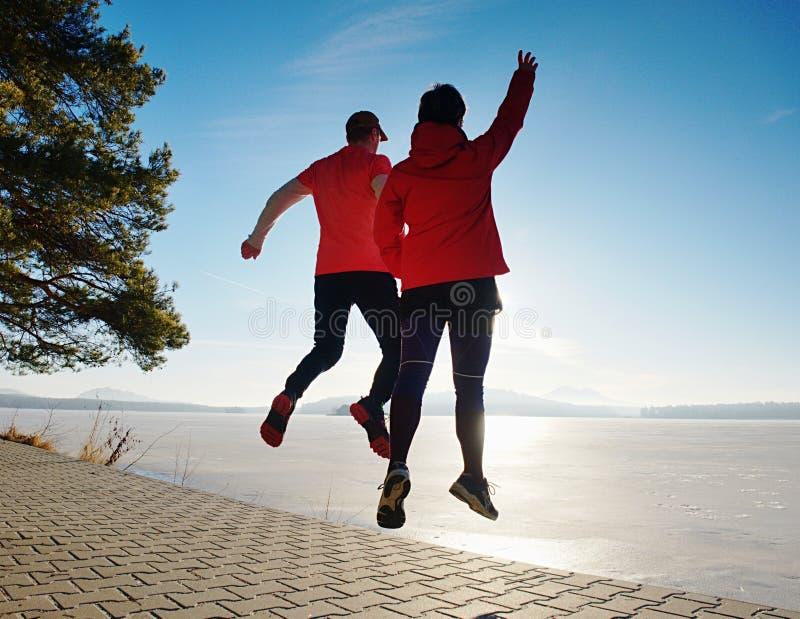 Salto felice delle coppie alla riva Vista di angolo basso ai corpi volanti fotografie stock
