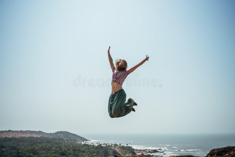 Salto feliz da eleva??o da mulher da alegria na praia em um vestu?rio desportivo fotos de stock royalty free