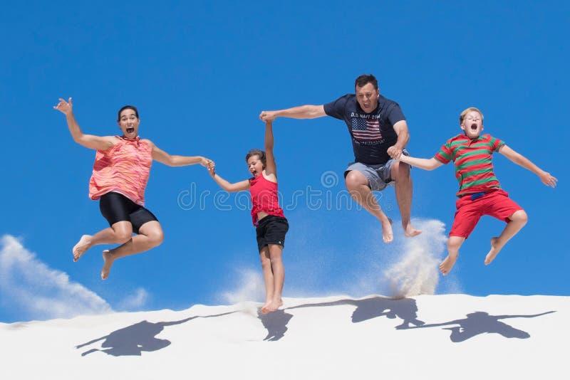 Salto feliz da família de quatro pessoas da duna de areia branca alta que tem o divertimento imagens de stock