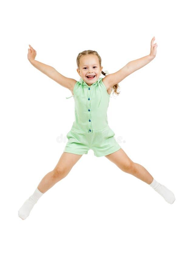 Salto feliz da menina da criança isolado no branco fotos de stock royalty free