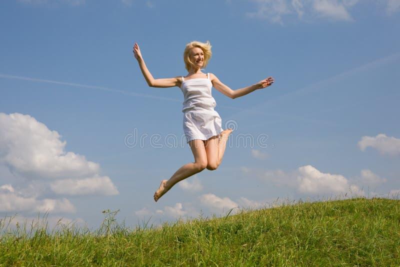 Salto feliz da mulher nova foto de stock