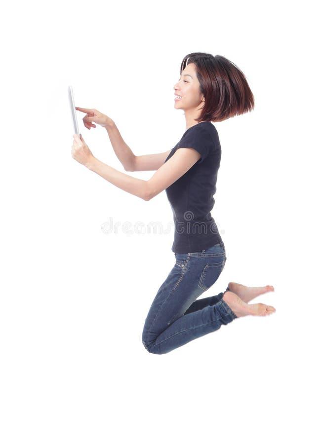 Salto feliz de la belleza joven y usar la PC de la tableta imágenes de archivo libres de regalías