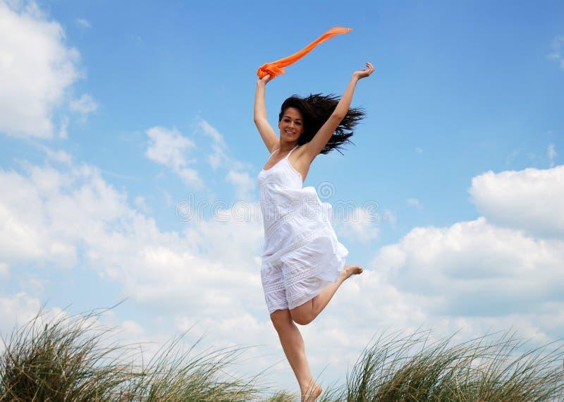 Salto feliz de la mujer foto de archivo