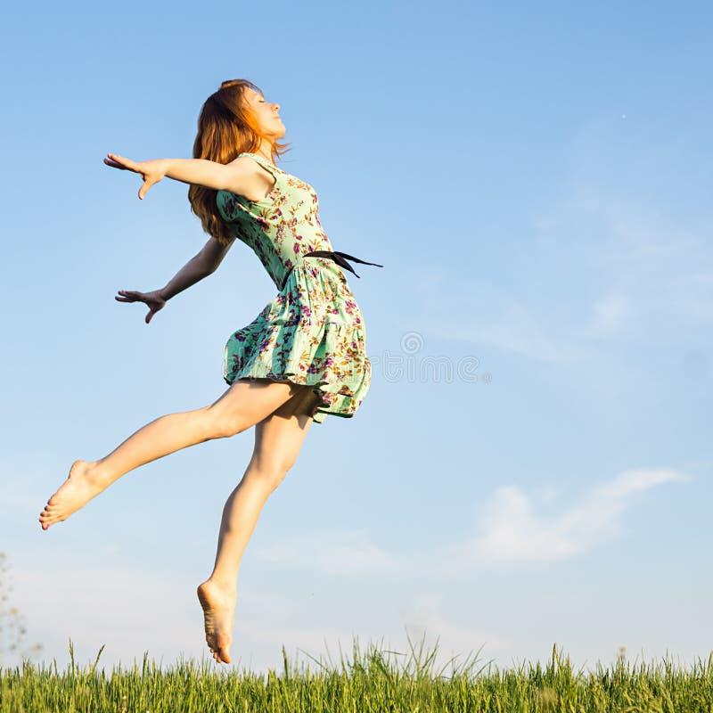 Salto feliz de la mujer joven fotos de archivo
