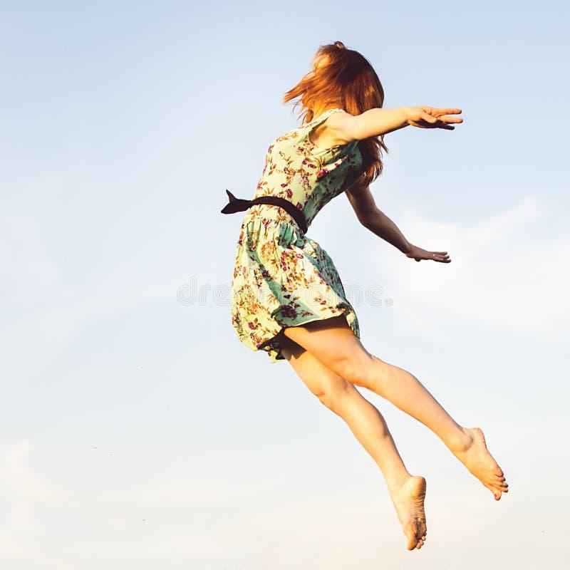 Salto feliz de la mujer joven imagenes de archivo