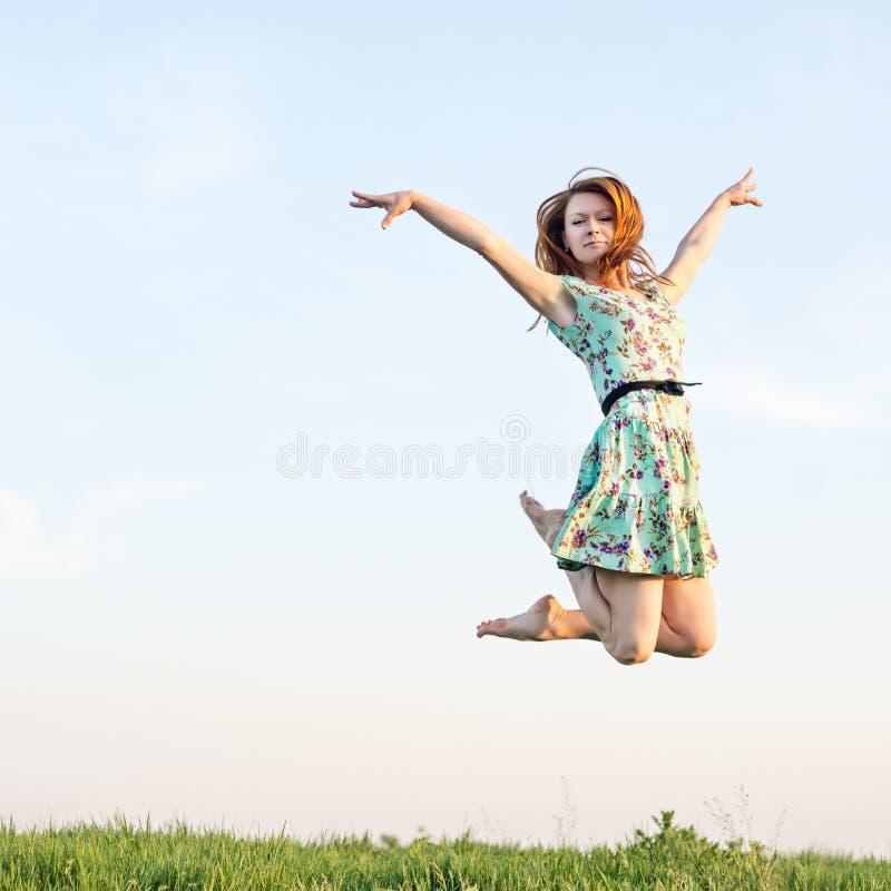 Salto feliz de la mujer joven fotografía de archivo