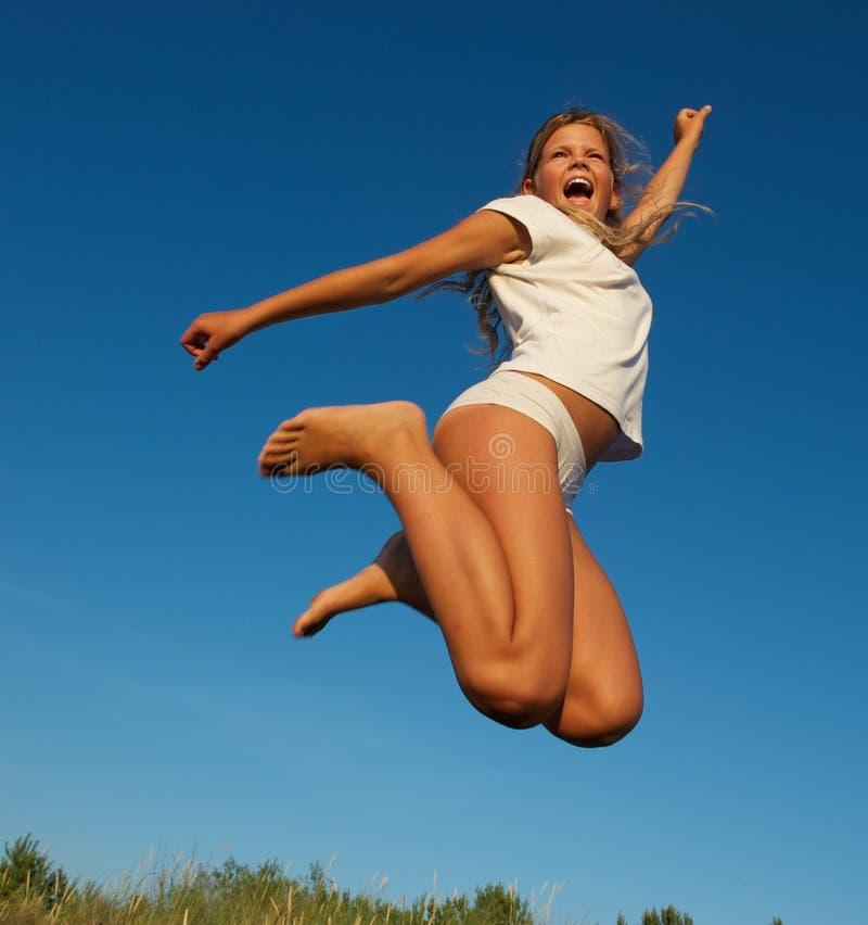 Salto feliz de la niña foto de archivo libre de regalías