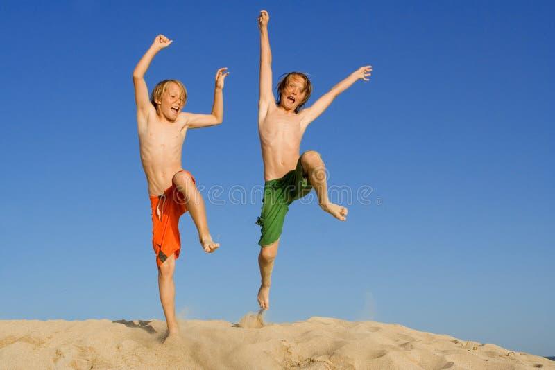Salto feliz de los niños o de los cabritos foto de archivo