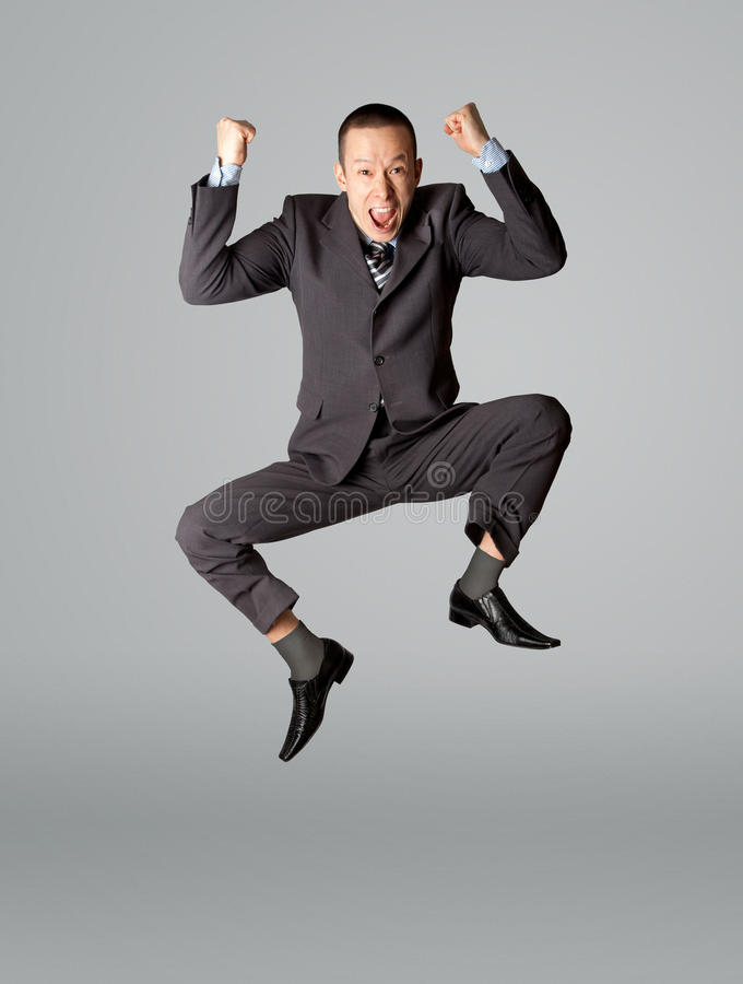 Salto feliz del hombre de negocios foto de archivo