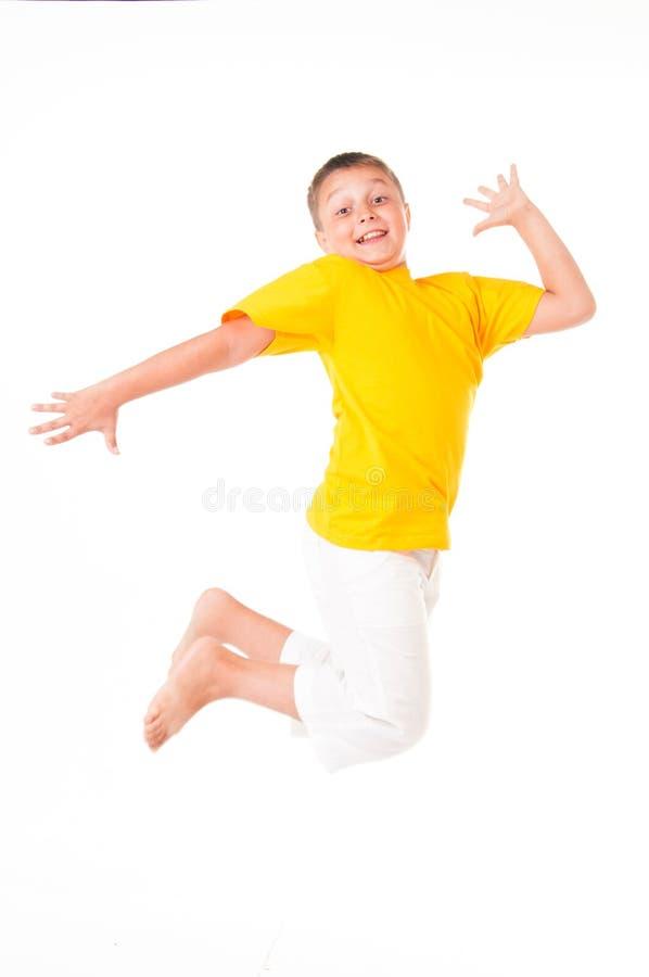 Salto feliz do rapaz pequeno isolado no fundo branco fotografia de stock royalty free