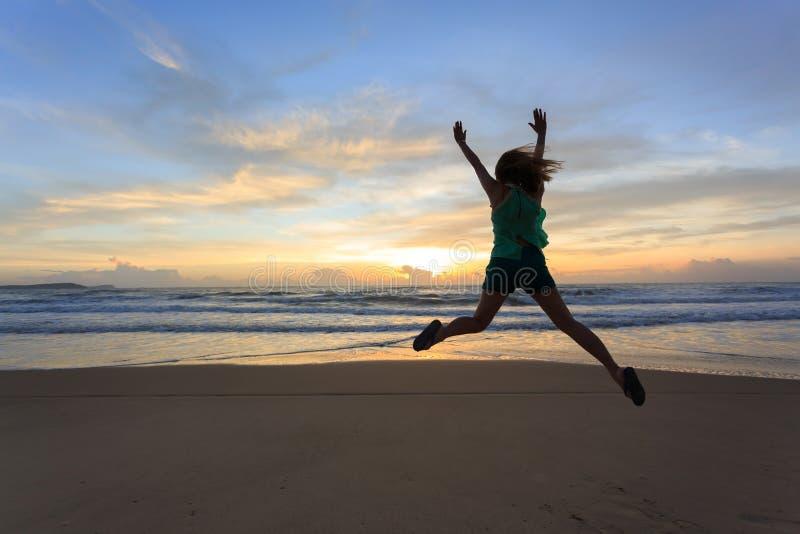 Salto feliz do viajante da mulher na praia com nascer do sol foto de stock