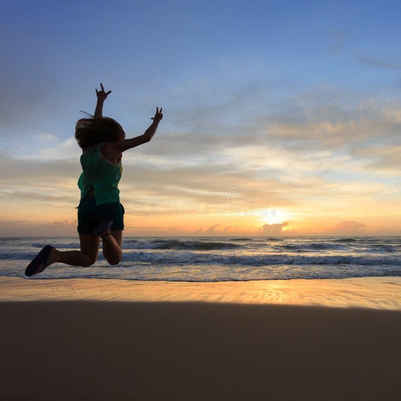 Salto feliz do viajante da mulher na praia com nascer do sol fotografia de stock