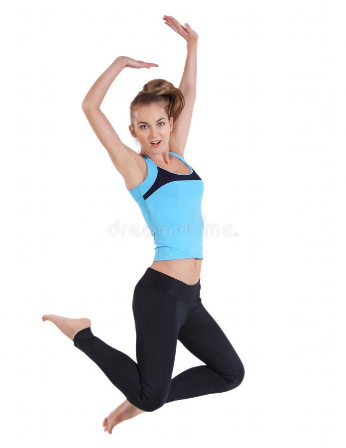 Salto feliz louro da mulher da aptidão foto de stock