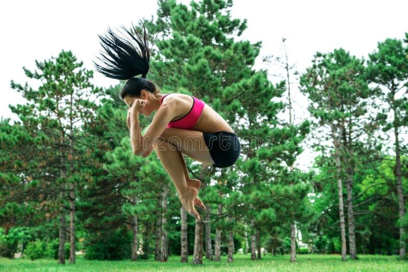 Salto femenino afuera en el parque fotografía de archivo