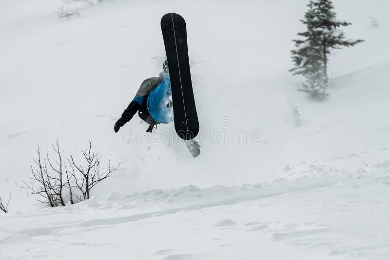 Salto freerider do Snowboarder de uma rampa da neve em um fundo da floresta e das montanhas fotos de stock royalty free