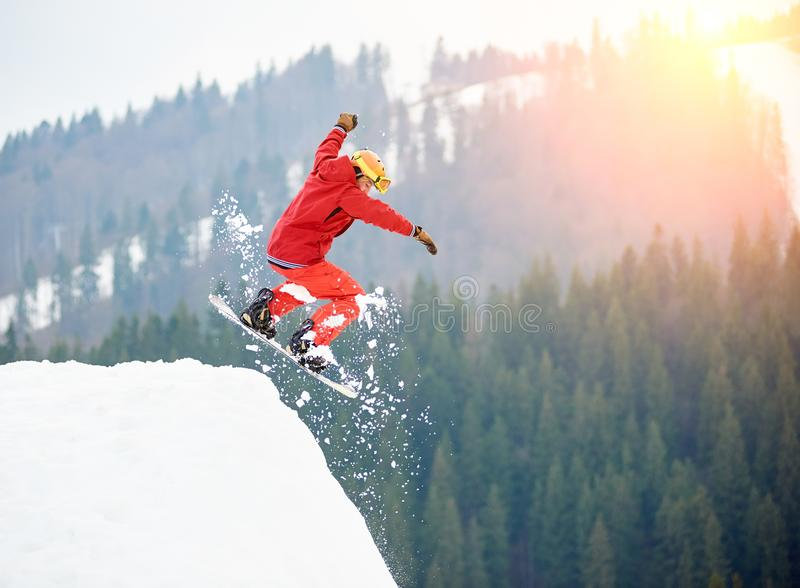 Salto freerider do snowboarder masculino da parte superior do monte nevado com snowboard fotos de stock