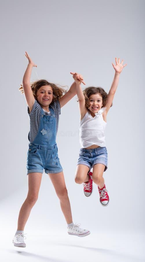Salto hiperactivo exuberante de dos chicas jóvenes imagen de archivo