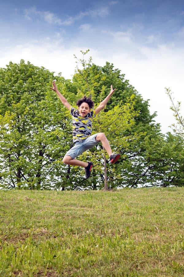 Salto joven ágil del muchacho alto en el aire imagen de archivo libre de regalías